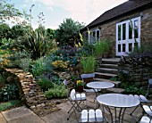 WINGWELL NURSERY  RUTLAND: PATIO AT THE BACK OF THE HOUSE WITH METAL CHAIRS AND TABLES. STONE WALLLS PLANTED WITH ACHILLEAS  PHORMIUM AND CRAMBE MARITIMA