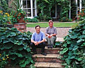 HALL FARM  LINCOLNSHIRE: PAM AND MARK TATAM ON THE STEPS IN FRONT OF THE HOUSE