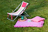 DESIGN BY CLARE MATTHEWS: DECKCHAIR ON LAWN WITH BLANKET  BOOK AND DRINKS