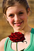 GIRL (AGED 13) HOLDING A RED ROSE AND SMILING