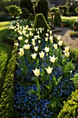 CHENIES MANOR GARDEN  BUCKINGHAMSHIRE: SUNDIAL AND SPRING BORDER PLANTED WITH FORGET-ME-NOTS AND TULIP DREAMING GIRL