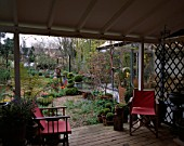 LISETTE PLEASANCE GARDEN  LONDON: VIEW FROM VERANDAH WITH PINK DECKCHAIRS ACROSS GRAVEL GARDEN WITH BOX TOPIARY  STIPA ARUNDINACEA  DECKED TERRACE AND TULIPS