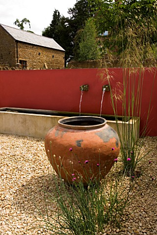 RICKYARD_BARN__NORTHAMPTONSHIRE_THE_GRAVEL_COURTYARD_IN_JUNE_WITH_LARGE_TERRACOTTA_CONTAINER__RED_WA