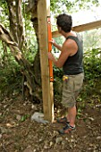 DESIGNER CLARE MATTHEWS: TREEHOUSE PROJECT - USING A SPIRIT LEVEL TO MAKE SURE WOODEN UPRIGHT IS STRAIGHT