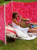 DESIGNER CLARE MATTHEWS: WIND BREAK SCREEN PROJECT - CLARE SITS IN THE WIND BREAK IN LAWN WITH CUSHIONS  BARBEQUE AND TRAY WITH DRINKS