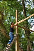 DESIGNER: CLARE MATTHEWS -  TREE HOUSE PROJECT - MAN USING SPIRIT LEVEL ON TREE HOUSE TIMBERS