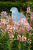 VEDDW HOUSE GARDEN  WALES: WOODEN CUT OUT OF BUZZARD IN BORDER WITH ROSE BAY WILLOWHERB (EPILOBIUM ANGUSTIFOLIUM)