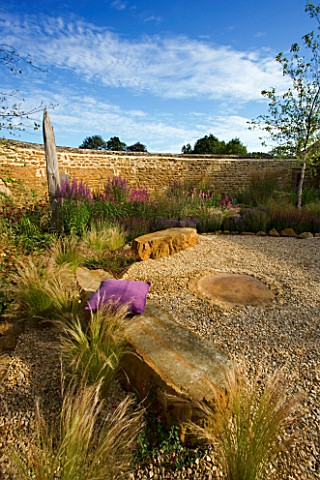 RICKYARD_BARN__NORTHANTS_GRAVEL_GARDEN_WITH_ROCKS__DRIFTWOOD_SCULPTURE_AND_STIPA_TENUIFOLIA