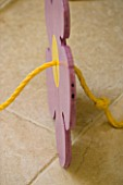 DESIGNER: CLARE MATTHEWS - FLOWER BUTTON SWINGS. YELLOW ROPE THROUGH CENTRE OF SEAT