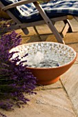 DESIGNER: CLARE MATTHEWS - BUBBLING BOWL PROJECT: TERRACOTTA WATER FEATURE ON PATIO BESIDE LAVENDER AND DECKCHAIR SHOWING GLASS BEADS AND WHITE MOSAIC