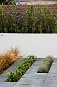 MINIMALIST GARDEN BY WYNNIATT-HUSEY CLARKE: WHITE WALL WITH PLANTING OF MISCANTHUS ZEBRINUS AND VERBENA BONARIENSIS. LINES OF FESTUCA GLAUCA  LIRIOPE MUSCARI AND STIPA TENUISSIMA