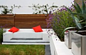 MINIMALIST GARDEN DESIGNED BY WYNNIATT-HUSEY CLARKE: RENDERED WHITE WALL WITH SEAT AND ORANGE CUSHIONS  VERBENA BONARIENSIS AND MISCANTHUS ZEBRINUS  AGAVE AMERICANA IN CONTAINER