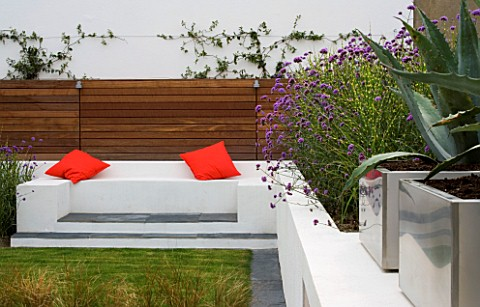 MINIMALIST_GARDEN_DESIGNED_BY_WYNNIATTHUSEY_CLARKE_RENDERED_WHITE_WALL_WITH_SEAT_AND_ORANGE_CUSHIONS