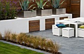 MINIMALIST GARDEN DESIGNED BY WYNNIATT-HUSEY CLARKE: GREY SLATE PATIO WITH THREE AGAVES IN METAL CONTAINERS  WHITE WALL  STIPA ARUNDINACEA AND WHITE TABLE