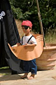 DESIGNER CLARE MATTHEWS: CHILDRENS PARTY - BOY ON PATIO DRESSED AS A PIRATE AND IN A PAPER SHIP BESIDE BLACK PIRATE TENT