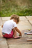 DESIGNER CLARE MATTHEWS: CHALK GAME - GIRL DRAWING WITH CHALK ON PATIO
