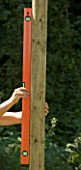 DESIGNER: CLARE MATTHEWS - TREEHOUSE PROJECT: USING SPIRIT LEVEL TO CHECK ON WOODEN UPRIGHT