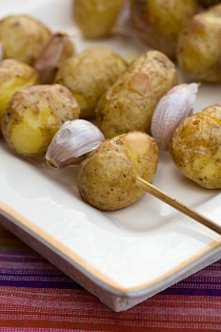 DESIGNER_CLARE_MATTHEWS__OUTDOOR_FOOD__ROASTED_WHOLE_POTATOES_WITH_GARLIC_CLOVES_ON_SKEWER