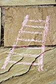DESIGNER: CLARE MATTHEWS: SNAKES AND LADDERS. CHALK DRAWING OF LADDER ON PATIO