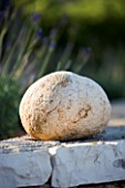 SPHERICAL ROCK SITS ON TOP OF STONE WALL IN GINA PRICES CORFU GARDEN.