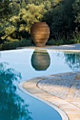 VIEW TOWARDS TERRACOTTA URN REFLECTED IN SWIMMING POOL IN GINA PRICES CORFU GARDEN.