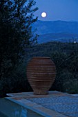 NIGHT VIEW ACROSS SWIMMING POOL TOWARDS TERRACOTTA URN WITH FULL MOON  IN GINA PRICES CORFU GARDEN.