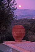 DUSK VIEW ACROSS SWIMMING POOL TOWARDS TERRACOTTA URN WITH FULL MOON  IN GINA PRICES CORFU GARDEN.