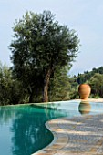 VIEW ACROSS SWIMMING POOL TOWARDS TERRACOTTA URN IN GINA PRICES CORFU GARDEN.