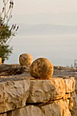 SPHERICAL STONES ON TOP OF DRY STONE WALL IN GINA PRICES CORFU GARDEN.
