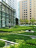 MARUNOUCHI HOTEL  TOKYO.FORMAL ROOF GARDEN WITH OFFICE BLOCKS-GRANITE SCULPTURES ON STONE PEDESTALS WITH GREEN CARPET.DESIGNER (ARCHITECT): MITSUBISHI JISHO SEKKEI INC.