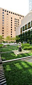 MARUNOUCHI HOTEL  TOKYO  JAPAN. MODERN FORMAL ROOF GARDEN WITH OFFICE BLOCKS - POLISHED GRANITE SCULPTURES ON STONE PEDESTALS WITH GREEN CARPET   DECKING AND TREES