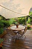 WOODEN DECKING WITH WOODEN TABLE AND CHAIRS  SHADE CANOPY  CANVAS. KATHY TAYLORS SMALL TOWN GARDEN  LONDON