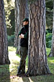 BRODSWORTH HALL  YORKSHIRE. ENGLISH HERITAGE. HEAD GARDENER DAN BOOTH BESIDE SOME PINE TREES