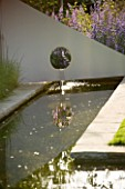 RICHARD JACKSONS GARDEN. DESIGNED BY CLARE MATTHEWS : WATER FEATURE - RECTANGULAR POND/POOL WITH METAL SAIL AND WATERFALL. REFLECTION
