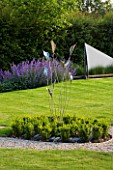 RICHARD JACKSONS GARDEN: EVENING LIGHT ON LAWN AND BORDER PLANTED WITH NEPETA WALKERS LOW  WATER RILL AND METAL SAILS  BOX BALLS AND METAL SCULPTURE. DESIGNER: CLARE MATTHEWS