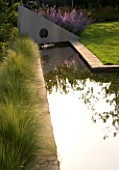 RICHARD JACKSONS GARDEN. DESIGNED BY CLARE MATTHEWS - WATER FEATURE - RECTANGULAR POOL/ POND WITH STIPA TENUISSIMA  METAL SAIL WITH WATERFALL. REFLECTION