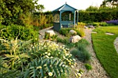 RICHARD JACKSONS GARDEN. DESIGNED BY CLARE MATTHEWS - GRAVEL BORDER BESIDE LAWN WITH CARDOON  ANTHEMIS SAUCE HOLLANDAISE   ROCKS  BLUE SUMMERHOUSE