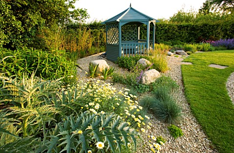 RICHARD_JACKSONS_GARDEN_DESIGNED_BY_CLARE_MATTHEWS__GRAVEL_BORDER_BESIDE_LAWN_WITH_CARDOON__ANTHEMIS