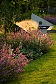 RICHARD JACKSONS GARDEN: EVENING LIGHT ON LAWN AND BORDER PLANTED WITH NEPETA WALKERS LOW  STACHYS BIG EARS. WATER RILL AND METAL SAILS. DESIGNER: CLARE MATTHEWS