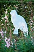 VEDDW HOUSE GARDEN  GWENT  WALES: DESIGNERS ANNE WAREHAM AND CHARLES HAWES - WOODEN CUT OUT BUZZARD SCULPTURE SURROUNDED BY ROSEBAY WILLOWHERB (EPILOBIUM ANGUSTIFOLIUM)