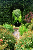 VEDDW HOUSE GARDEN  GWENT  WALES: DESIGNERS ANNE WAREHAM AND CHARLES HAWES - VIEW THOUGH HORNBEAM TUNNEL TO CUT OUT DOVE SCULPTURE WITH BIRD BATH IN THE FOREGROUND