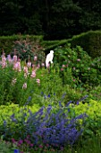 VEDDW HOUSE GARDEN  GWENT  WALES: DESIGNERS ANNE WAREHAM AND CHARLES HAWES - THE CRESCENT BORDER WITH BUZZARD CUT OUT SCULPTURE  EPILOBIUM ANGUSTIFOLIUM  ALCHEMILLA AND NEPETA