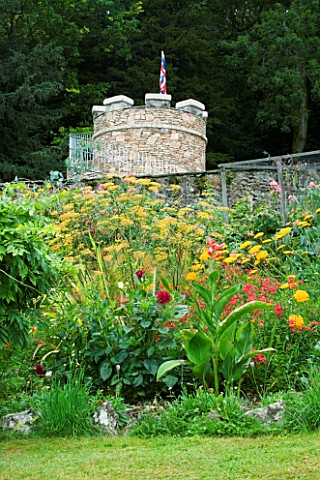 YEWBARROW_HOUSE_GARDENS__CUMBRIA__HOT_BORDER_WITH_CANNA__DAHLIA_AND_PHORMIUM_WITH_THE_NEW_ROUND_TOWE