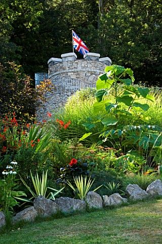 YEWBARROW_HOUSE_GARDENS__CUMBRIA__TROPICAL_BORDER_WITH_THE_NEW_ROUND_TOWER