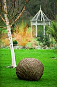 WOODPECKERS  WARWICKSHIRE  WINTER: WOVEN WILLOW BALL SCULPTURE IN LAWN WITH BETULA HERGEST AND SUMMERHOUSE
