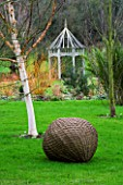 WOODPECKERS  WARWICKSHIRE  WINTER: WOVEN WILLOW BALL SCULPTURE WITH BETULA HERGEST AND A WOODEN PERGOLA
