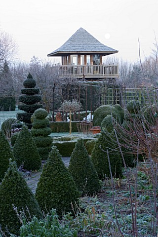 WOODPECKERS__WARWICKSHIRE__WINTER_THE_FORMAL_TOPIARY_GARDEN_IN_FROST_WITH_SUMMERHOUSE_TOWER_BEHIND