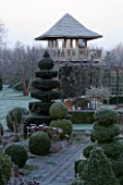 WOODPECKERS  WARWICKSHIRE  WINTER: THE FORMAL TOPIARY GARDEN IN FROST WITH SUMMERHOUSE TOWER BEHIND