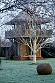 WOODPECKERS  WARWICKSHIRE  WINTER: FORMAL GARDEN IN FROST WITH LAWN  WOVEN WILLOW SCULPTURE  BETULA UTILIS VAR JACQUEMONTII AND WOODEN SUMMERHOUSE
