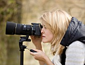 BLOND HAIRED GIRL WITH 35MM SLR DIGITAL CAMERA IN A GARDEN